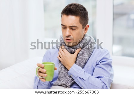 healthcare, people and medicine concept - ill man with flu coughing and drinking hot tea from cup at home - stock photo