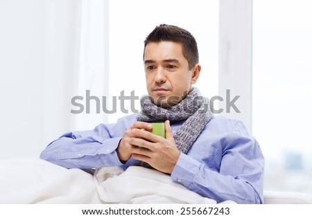 healthcare, people and medicine concept - ill man with flu drinking hot tea from cup at home - stock photo
