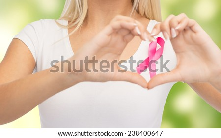 healthcare, people, charity and medicine concept - close up of young woman in blank white t-shirt with pink breast cancer awareness ribbon showing heart shape over green background - stock photo