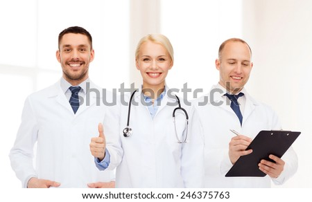 healthcare, people, gesture and medicine concept - group of doctors with stethoscope and clipboard showing thumbs up over clinic background - stock photo