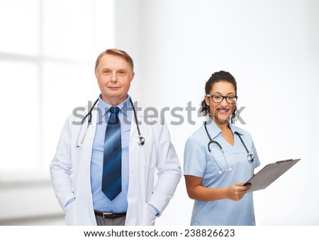 healthcare, profession and medicine concept - smiling doctors with clipboard and stethoscopes over clinic background - stock photo