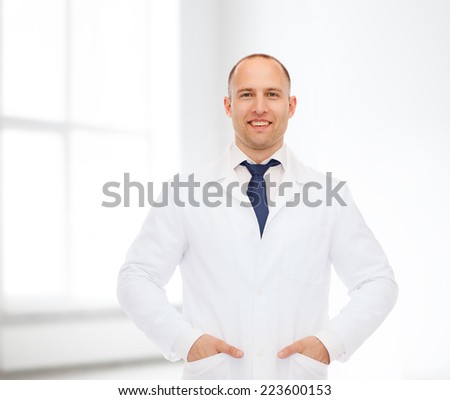 healthcare, profession and medicine concept - smiling male doctor in white coat over white room background - stock photo