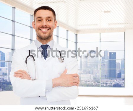 healthcare, profession, people and medicine concept - smiling male doctor with stethoscope in white coat over clinic room background - stock photo
