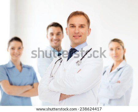 healthcare, profession, teamwork, people and medicine concept - smiling male doctor with stethoscope in white coat over over group of medics - stock photo