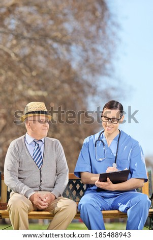 Healthcare professional doing a medical check on a senior adult in park  - stock photo