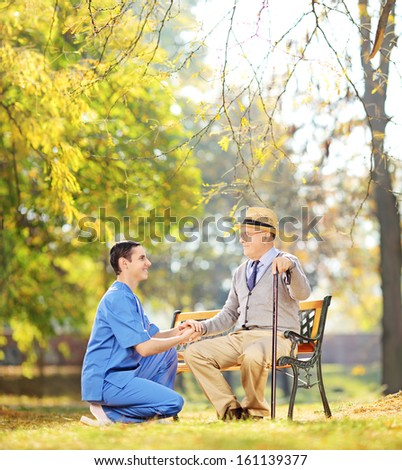 Healthcare professional helping senior man sitting on a wooden bench outside, shot with a tilt and shift lens - stock photo
