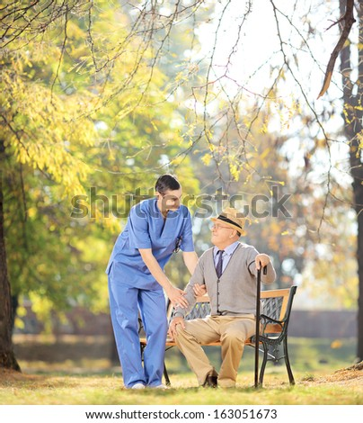 Healthcare professional talking senior man seated on wooden bench outside, shot with a tilt and shift lens - stock photo