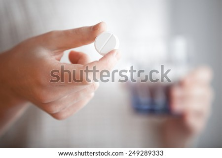 Healthcare, treatment, supplements. Female patient arms holding one round pill and glass of water before taking medication, shallow depth of field, focus on medicine - stock photo