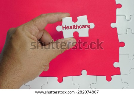 Healthcare word on white puzzle - Business Concept - stock photo