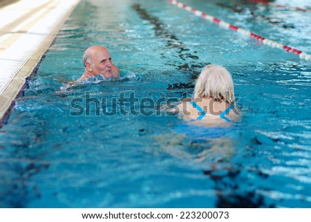 Healthy active active senior couple swimming together in the pool - stock photo