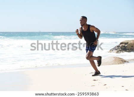 Healthy active african american man running by water on the beach - stock photo