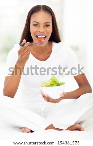 healthy african woman sitting on bed and eating salad - stock photo