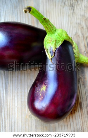 Healthy and delicious purple eggplants on wooden background - stock photo