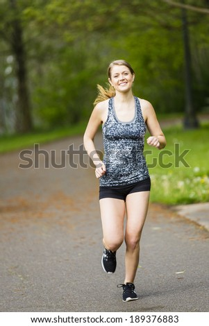 Healthy and fit model smiling and jogging outdoors - stock photo