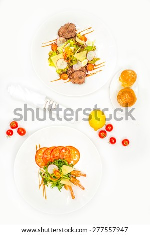 Healthy and fresh salad with shrimps and vegetables serving on the plate and plate of salad with meat - stock photo