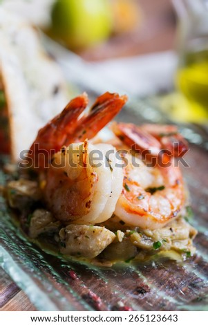Healthy and fresh salad with shrimps and vegetables serving on the plate on a wooden table in a restaurant with decor - stock photo