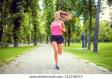 healthy and happy woman running in urban park with headphones and music  - stock photo
