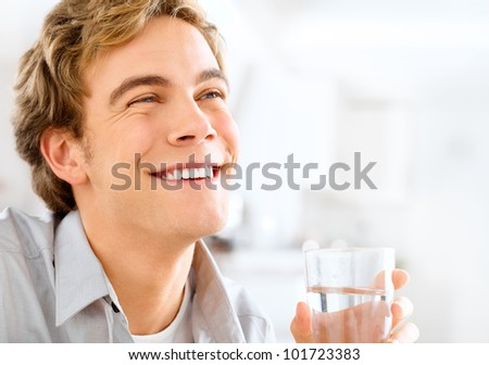 Healthy and happy young man holding glass of water while relaxin - stock photo