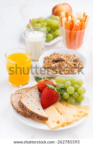 healthy and nutritious breakfast with fresh fruits and vegetables on white table, vertical - stock photo