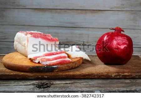 Healthy and unhealthy food. Fatty bacon and pomegranate on wooden chopping board - stock photo
