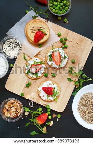 Healthy Appetizer Small Sandwiches Cottage Cheese Strawberry Seeds Peas Almond Flakes Sprouts Summer Fruits Vegetables on Crisp Cookies Top view - stock photo