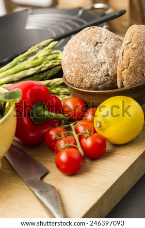 Healthy assortment of fresh vegetables including red bell pepper, lemon, asparagus tips and tomatoes with wholegrain rolls on a wooden kitchen counter with a sharp knife - stock photo