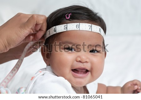 Healthy baby getting her head circumference measured, routine doctor checkup - stock photo