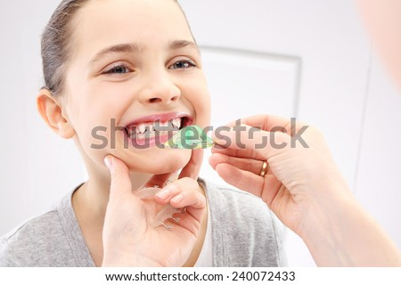 Healthy, beautiful smile, the child to the dentist. Portrait of a little girl with orthodontic appliance  - stock photo