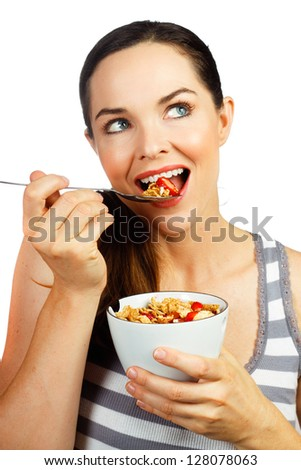 Healthy beautiful woman eating a nice bowl of cereal and strawberries for breakfast. Isolated on white. - stock photo