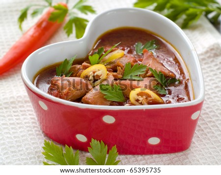 Healthy beef stew in heart shaped bowl  with parsley and chili - stock photo