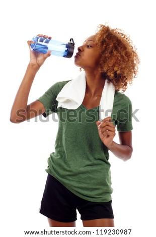 Healthy black woman with gym towel drinking out of water bottle isolated over white - stock photo