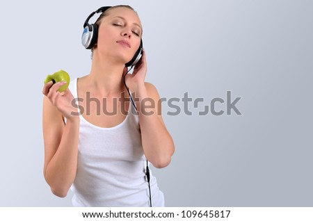 Healthy blondy happy woman holding a green apple and listening to music - stock photo