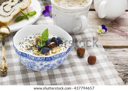 Healthy breakfast. A cup of yogurt with granola, seeds, nuts and berries, pollen portions served with a cup of coffee for a family breakfast. The concept of organic nutrition - stock photo