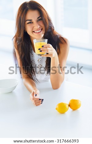 Healthy breakfast. Attractive cheerful young woman drinking orange juice in her kitchen and smiling at the camera. Wellness concept - stock photo