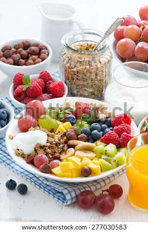 healthy breakfast - berries, fresh fruit and cereal on the plate, vertical - stock photo