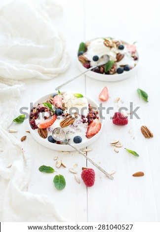 Healthy breakfast. Berry crumble with fresh blueberries, raspberries, strawberries, almond, walnuts, pecans, yogurt, and mint in ceramic plates over white wooden surface, top view - stock photo