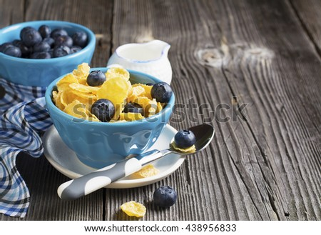 Healthy breakfast. Blue portioned ceramic bowls with corn flakes with fresh blueberries on a dark wooden background with blue creamer on a checkered napkin. selective focus - stock photo