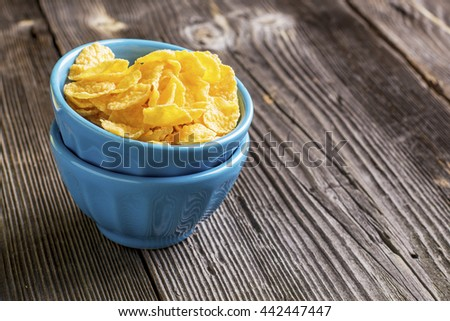 Healthy breakfast. Blue portioned ceramic bowls with corn flakes with on dark wooden background. selective focus - stock photo