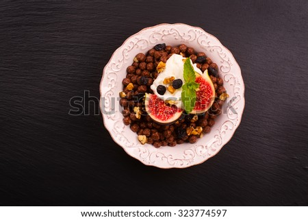 Healthy breakfast: bowl of chocolate balls with yoghurt and fresh figs on black stone table. Selective focus - stock photo