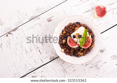 Healthy breakfast: bowl of chocolate balls with yoghurt and fresh figs on white wooden table. Selective focus. Top view - stock photo