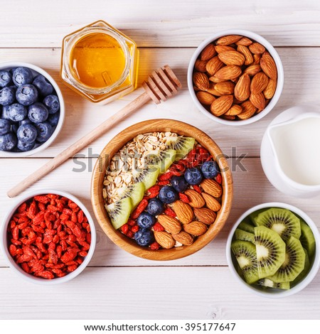 Healthy breakfast - bowl of oat flakes with fresh fruit, almond and honey, selective focus. - stock photo