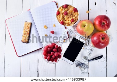 Healthy breakfast cereals, berries, apples and cereal bars on a table top view.Concept of healthy food, accessories for recording diet: a smartphone, notebook, pen and measuring tape. - stock photo