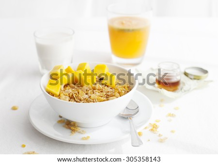 Healthy breakfast. Corn flakes, muesli, granola with mango cubes with a glass of milk and fresh orange juice on a white textile background - stock photo