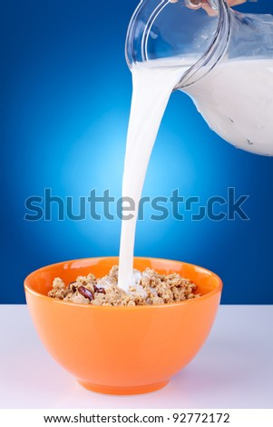 Healthy Breakfast-Cornflakes and Milk Splash on blue background - stock photo