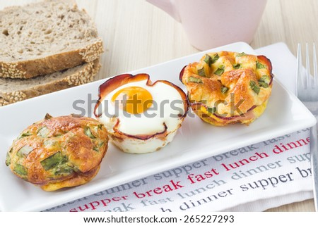 Healthy breakfast egg muffins with toast and tea or coffee on a wooden kitchen table. - stock photo