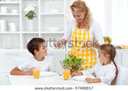 Healthy breakfast for happy life - mother serving kids with salad - stock photo