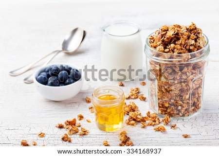 Healthy breakfast. Fresh granola, muesli in a glass jar with yogurt, fresh blueberry and honey on a white wooden background  - stock photo