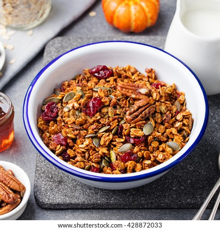 Healthy breakfast. Fresh granola, muesli with pumpkin,pecan nuts,cranberries and maple syrup in white bowl - stock photo