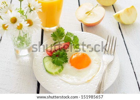 Healthy breakfast: fried egg and apple - stock photo