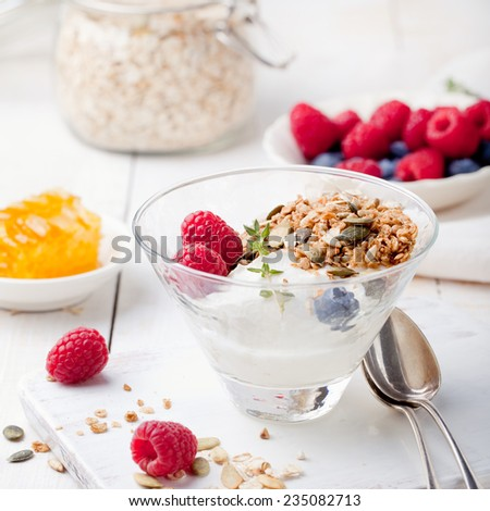 Healthy breakfast. Granola with pumpkin seeds, honey, yogurt and fresh berries in a ceramic bowl on white background. - stock photo